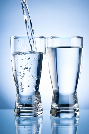 Pouring water into glasson and Glass of water on a blue background photo