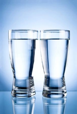vasos de agua: Dos vasos de agua sobre un fondo azul