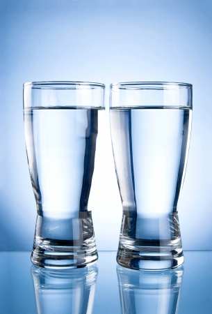 water level: Two glasses of water on a blue background