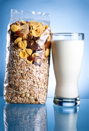 cornflakes: Fresh Glass of Milk and Closed Pack of muesli on a blue background