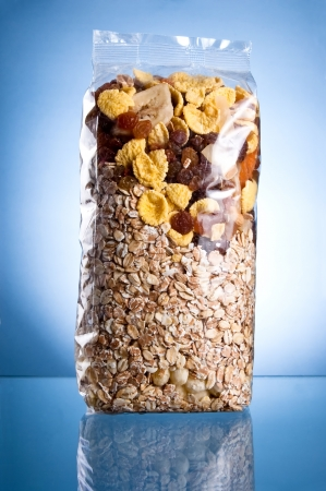 Pack of muesli  Dry breakfast, mixture of corn flakes and dried fruit  on a blue background photo