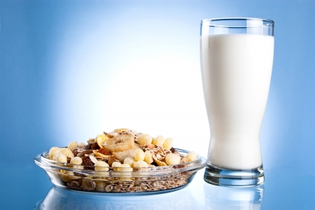 Dish of muesli and glass of fresh milk on a blue background photo