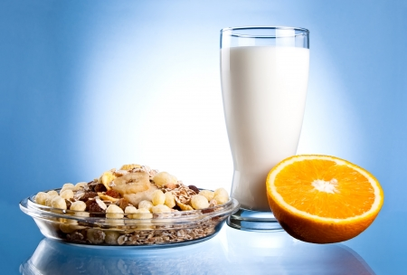 citrus family: Dish of muesli, glass of fresh milk and Half of juicy orange on a blue background
