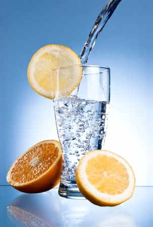 Mineral water glass with lemon and orange on a blue background photo