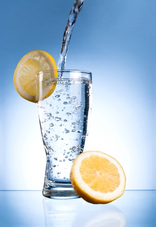 glass of water: Mineral water glass with lemon on a blue background