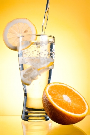 Pouring of mineral water in glass with a lemon and orange on a yellow background photo
