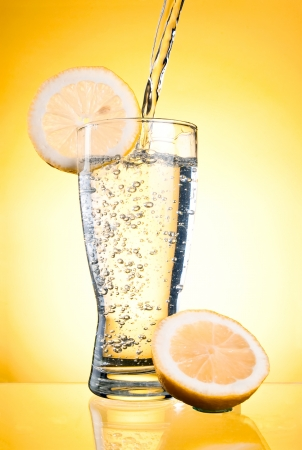 Pouring of mineral water in glass with a lemon on a yellow background photo