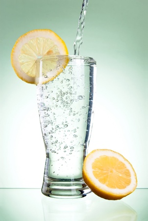Pouring of mineral water in glass with a lemon on a Green background photo