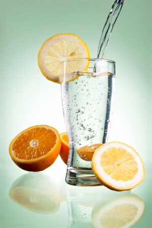 Pouring of mineral water in glass with a lemon and orange on a green background photo