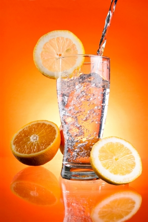 overflowing: Pouring of mineral water in glass with a lemon and orange on a Orange background