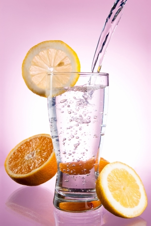 Pouring of mineral water in glass with a lemon and orange on a pink background photo