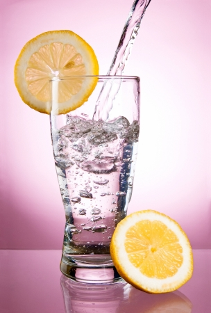 Pouring of mineral water in glass with a lemon on a pink background photo