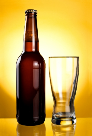 Empty glass and Beer Brown Bottle on a yellow background photo