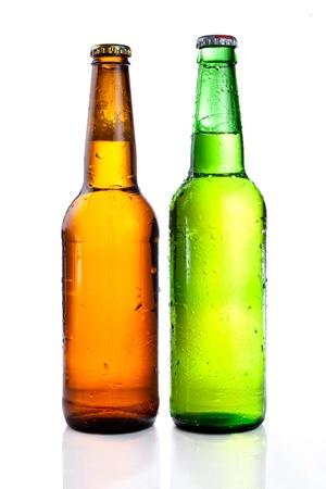 Cerveza verde y marrón botella con bebida gotas sin etiqueta en un fondo blanco Foto de archivo