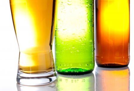 Bottom of the brown and green bottles with a full glass of beer photo