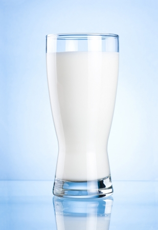 Glass of milk on blue background photo