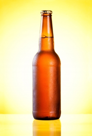 condensate: Brown full bottle fresh cold beer covered with condensate on yellow background Stock Photo