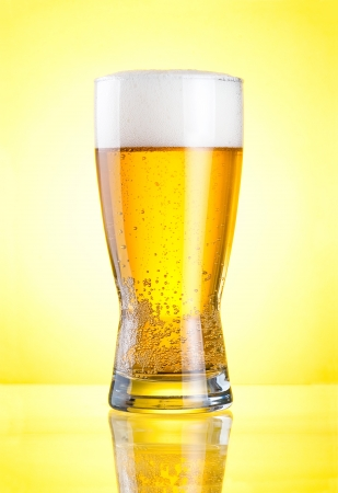 draught: Glass of fresh lager beer close-up with froth over yellow background