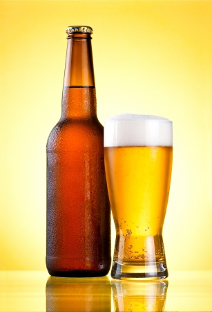 condensate: Brown full bottle covered with condensate and glass fresh cold beer on yellow background