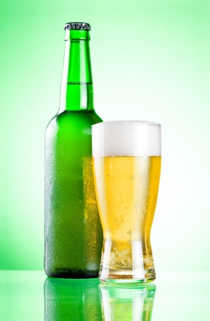 condensate: Chilled green bottle with condensate and a glass of beer lager on a green background Stock Photo
