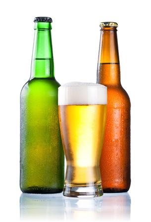 茶色と緑色のボトルの凝縮の完全かつ新鮮な冷たいビール、白い背景で隔離のガラスで覆われています。