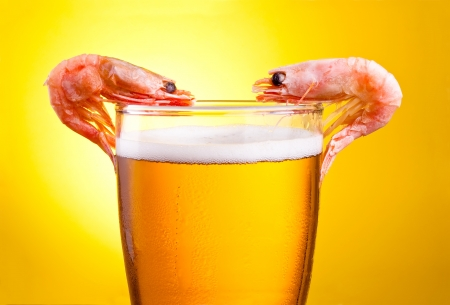 Two Cooked Shrimp in a glass of beer with foam on a yellow background photo