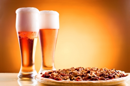 ビールとピザ黄色の背景上の 2 枚のガラス
