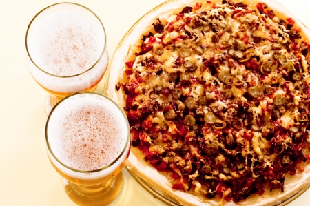 Top view Two glass of beer and pizza over yellow background