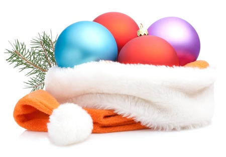 Christmas Red, Purple, Blue Baubles in Traditional Santa Hat and branch of tree Isolated on white background photo