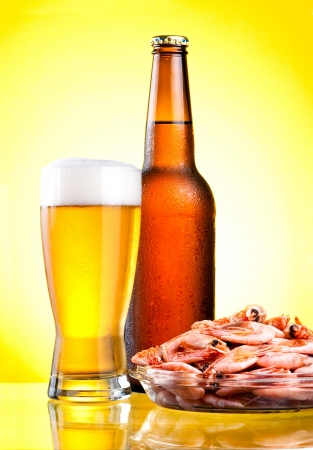 Brown bottle of beer with a condensate, a glass and a plate of boiled shrimp on a yellow background photo