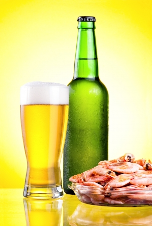 condensate: Green bottle of beer with a condensate, a glass and a plate of boiled shrimp on a yellow background