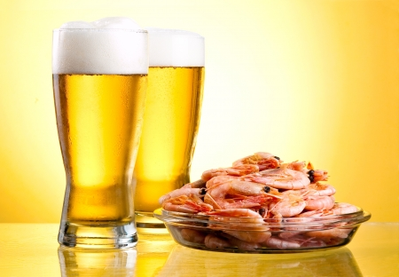 Two  glass of beer and cooked shrimp on a plate on a yellow background