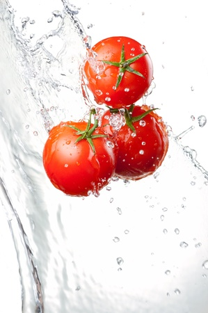 Three Fresh red Tomatoes in splash of water Isolated on white background Фото со стока