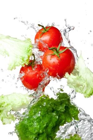 lechuga: Tres tomates frescos de color rojo y la lechuga en las salpicaduras de agua aisladas sobre fondo blanco