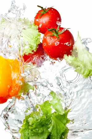 ensalada de verduras: Tres tomates frescos de color rojo, el pimiento amarillo y la lechuga en las salpicaduras de agua aisladas sobre fondo blanco