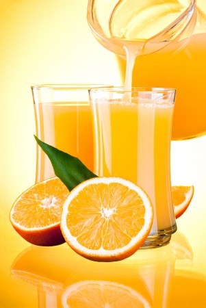 Juice to pour from pitcher, Oranges with leaves on yellow background Standard-Bild