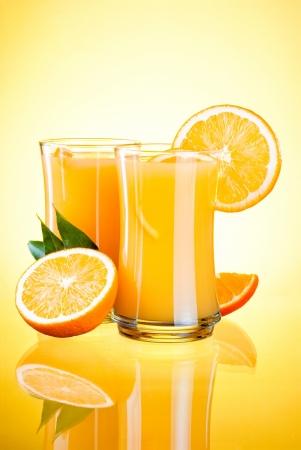 verre de jus d orange: Deux verres de jus d'orange frais, oranges et demi et les feuilles sur fond jaune Banque d'images