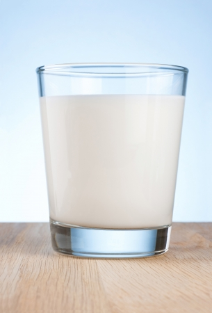 full frames: Glass of fresh milk is wooden table on a blue background