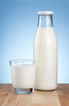 milk bottle: Bottle of fresh milk and glass is wooden table on a blue background