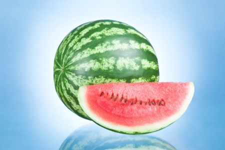 Ripe Watermelon and Slice isolated on a blue background photo