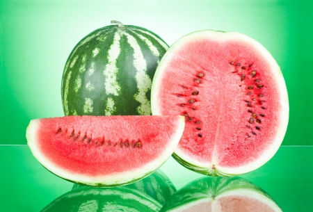 Watermelon, half and Slice on a green background photo