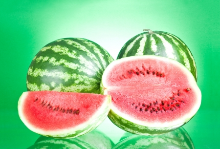 Two watermelon, half and Slice on a green background photo
