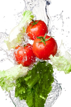 Three Fresh red Tomatoes and lettuce in splash water Isolated on white background