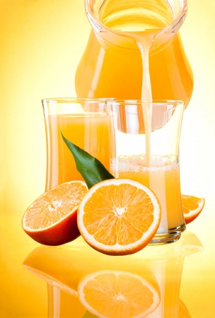 glass half full: Juice to pour from pitcher, Oranges with leaves on yellow background Stock Photo