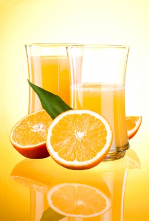 gelb: Two Glasses of Fresh Orange juice, half oranges and the leaves on yellow background