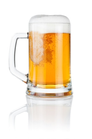 Pouring fresh beer into mug isolated over a white background Фото со стока