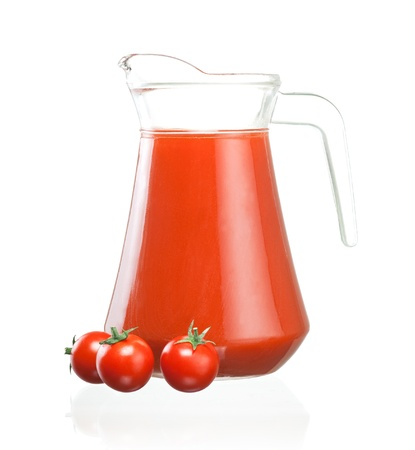 Jug of tomato juice and three fruits with green leaves isolated