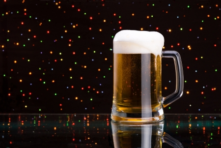 overflowing: Mug fresh beer with cap of foam on colored light background
