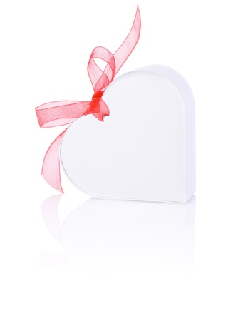 White gift in the form of heart with a bow of red ribbon Isolated on white background photo