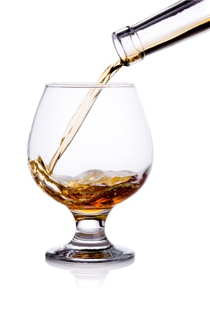 intoxicant: Pouring from bottle of cognac in glass isolated on white background Stock Photo